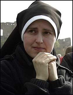 BØNN: En nonne ber mens hun følger begravelsen på storskjerm i Roma. Foto: AP
