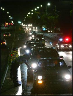 KONTROLL: Politiet opprettet veisperringer i forstaden Cronulla og gjennomsøkte flere hundre biler på jakt etter voldelige opprørere. Foto: AFP.