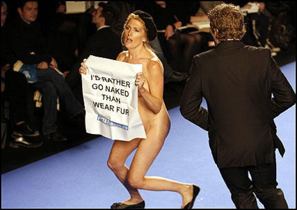 ELLEVILT: En mann iler til for å stanse den nakne kvinnen fra å spolere moteshowet i Paris i går. Foto: Reuters