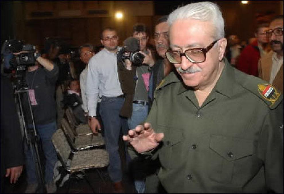 FOR RETTEN: Iraks tidligere visestatsminister, Tariq Aziz, fotografert foran et bilde av diktatoren Saddam Hussein i 2006. Aziz blir nå stilt for retten i Bagdad, tiltalt for drap på 22 kjøpmenn i 1992. Foto: AP