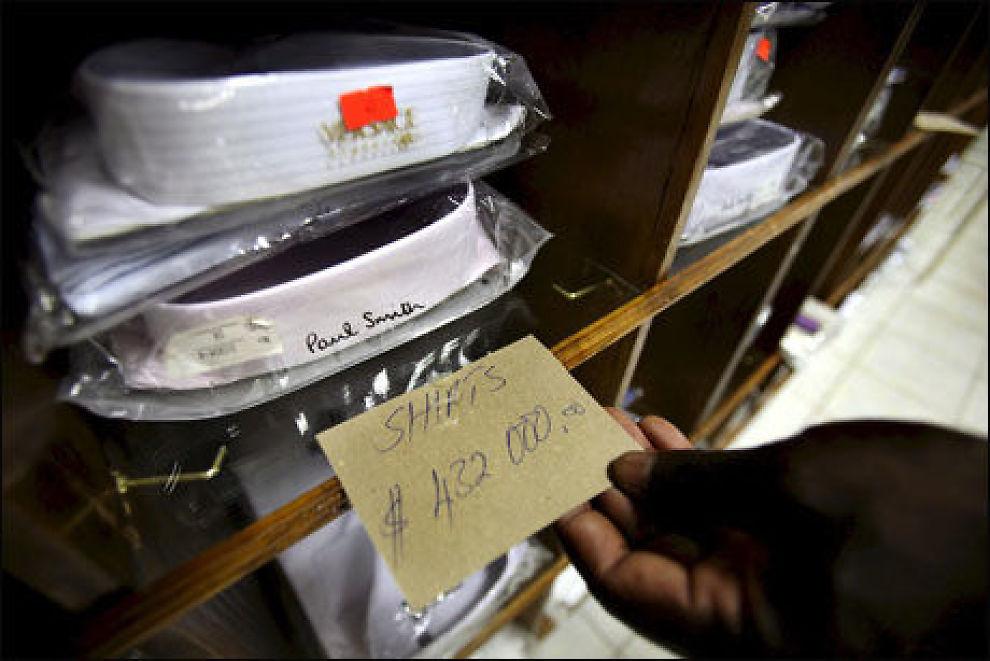 DYRT: En kunde sjekker prisen på ei skjorte i en butikk i Zimbabwes hovedstad Harare torsdag. Inflasjonen i landet har nådd 231 millioner prosent. Foto: EPA