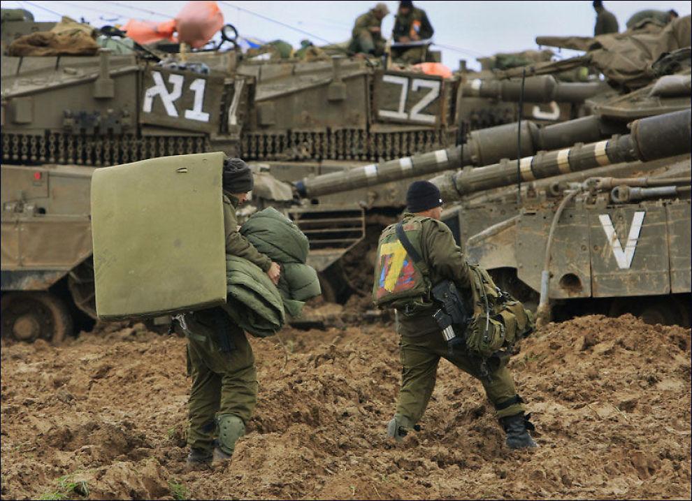 STÅR KLARE: Israelske soldater bærer utstyr, ved grensen til Gaza-by. I bakgrunnen kan man se militære kjøretøy som står klare. En bakkekrig er sannsynligvis det neste steget fra israelsk side. Foto: AP
