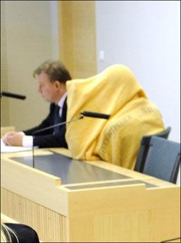 TILTALT: Her gjemmer den tiltalte gutten seg under et gult pledd under fengslingsmøtet. Foto: Ola Axman/Aftonbladet
