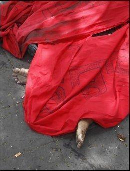 TILDEKKET: Et rødt teppe dekker til en demonstrant som mistet livet da militæret trengte seg inn i rødskjortenes leir onsdag. Foto: Reuters