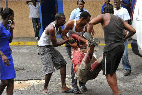 SÅRET: To menn hjelper en mann som er blitt såret i gatekampene i Kingston. Foto: EPA