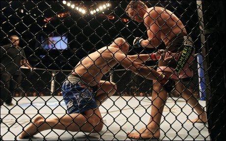 GITTER OG STAS: Slik kan det se ut i buret under en kamp. Her er det Rich Franklin, (til h.) som slår ut Chuck Liddell i en kamp tidligere i år. Foto: AP Photo/The Canadian Press