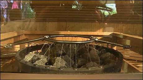 VANNDAMP: En halvliter vann ble sprøytet på disse glovarme steinene hvert 30.sekund, noe som gjorde saunaen enda mer uutholdelig. Foto: AFP