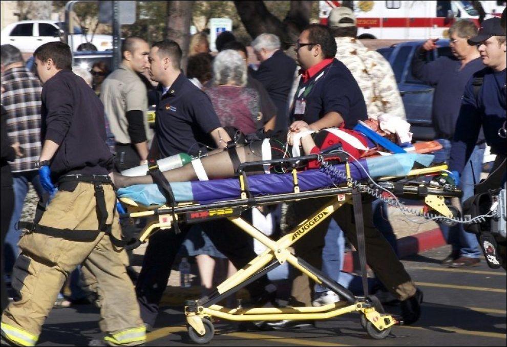 HOLDER HENDER: Her er Gabrielle Giffords på vei inn i ambulansen etter skytedramaet. Mannen som holder henne i hånden skal være Daniel Hernandez - som får æren for å ha reddet livet hennes. Foto: AP
