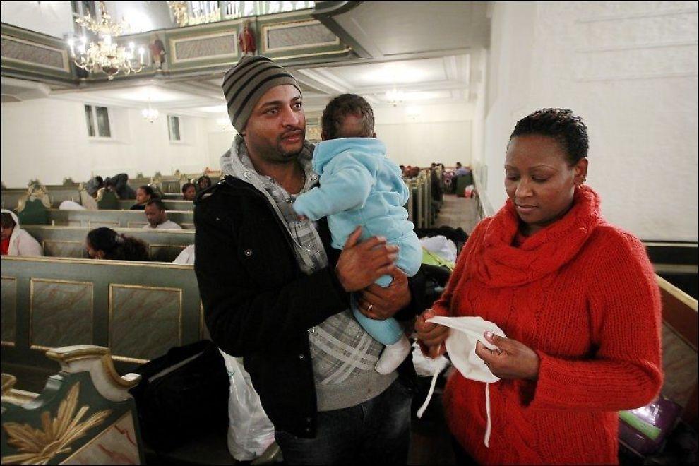 VIL BLI: Abiye Hagos (f.v.), Christian Abiye (6 mnd.), Opse Dihnsa og et femtitalls andre etiopere oppholdt seg fortsatt i Oslo domkirke sent mandag kveld. Foto: Scanpix