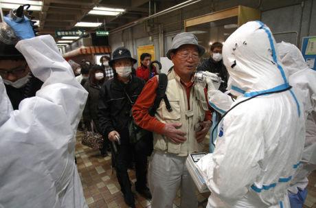 STRÅLESJEKKES: En av de evkuerte i området rundt Fukushima Daiichi-kraftverket sjekkes for radioaktiv stråling. Foto: Ap