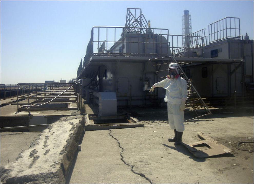 MASSIV SPREKK: Her peker arbeiderne på en sprekk i atomkraftverket Fukushima Daiichi. De siste ukene har det lekket radioaktivt vann ut fra slike sprekker. Foto: ap