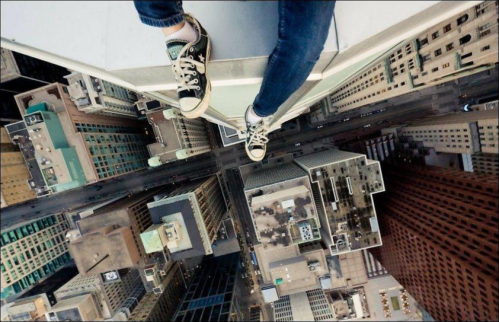 HØYT OPPE: Fotograf Tom Ryaboi har ikke høydeskrekk, og tar her bilde ned fra en høy bygning for å oppleve det «ultimate rushet». Foto: TOM RYABOI/WENN