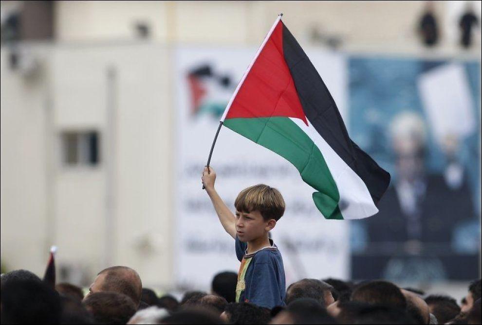 DEMONSTRERER: En gutt holder et palestinsk flagg under en demonstrasjon i byen Ramallah på den okkuperte Vestbredden. Foto: REUTERS / Mohamad Torokman / SCANPIX