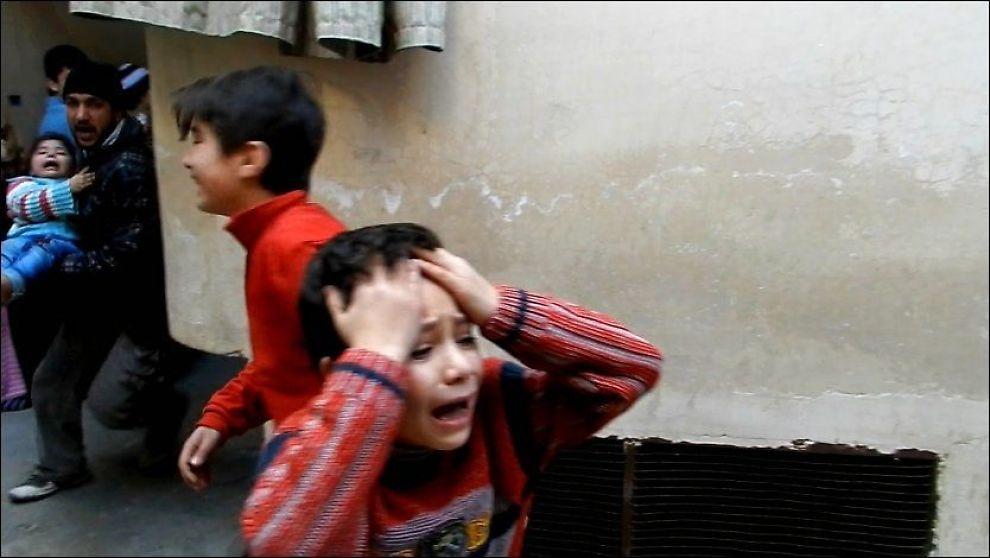 GRÅTENDE BARN: En mann bærer et lite barn, mens to små gråtende gutter løper i gatene, i Bab Tudmor-nabolaget i byen Homs i Syria 25. februar 2012. Foto: AFP