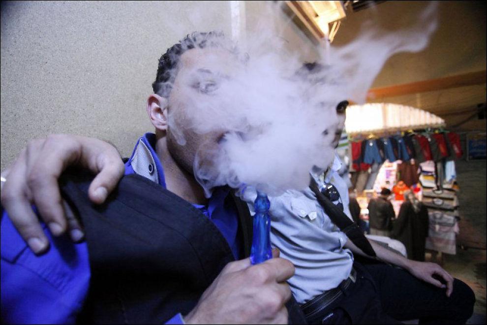 GJEMMER SEG: Unge irakere som regner seg selv som «emoer» skjuler identiteten sin bak damp fra en tradisjonell vannpipe i byen Najaf. Najaf ligger 16 mil fra Bagdad, der 58 antatt homofile skal ha blitt drept de siste seks ukene. Foto: Alaa al-Marjani/AP Foto: