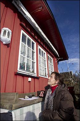 HUSEIER: Anne Margrethe Thomassen med meteoritten som slo hull i taket på huset hennes på Rodeløkka kolonihage i Oslo. Øverst på bildet sees hullet i taket. Foto: Scanpix