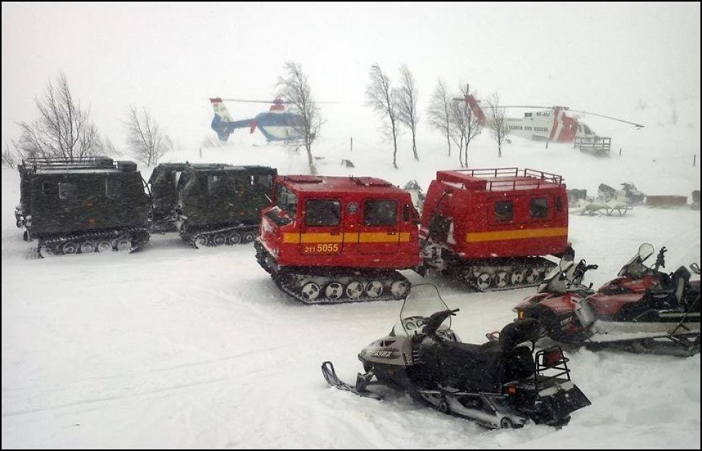 VANSKELIGE FORHOLD: Her står to helikoptre på bakken ved Kebnekaise fjellstasjon. Værforholdene har gjort letingen etter Hercules-flyet svært krevende. Foto: HÅKAN HAMMARBERG
