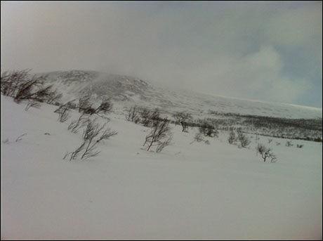 KRAFTIG VIND: Bak dette fjellpartiet letes det nå etter det savnede Hercules-flyet. Foto: Foto: EIRIK LINAKER BERGLUND