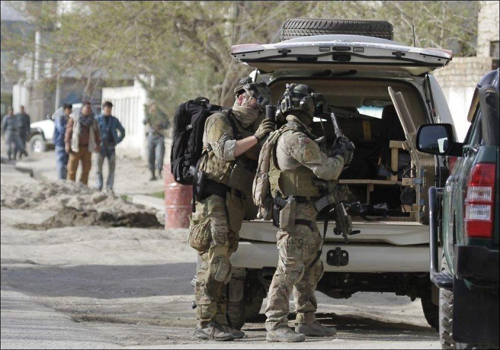 DELTAR: Norske soldater deltar også i kampene i Kabul. Her får en norsk soldat hjelp til å ordne utstyret sitt under dagens Taliban-angrep i den afghanske hovedstaden. Foto: Ahmad Jamshid/AP