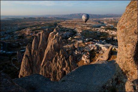 EN HVIT OG BLÅ BALLONG: Varmluftsballong er en av de mest populære måtene å se Cappadocia på. Her glir en av dem stille forbi klippeborgen i Uchisar rett før solnedgang. Foto: GJERMUND GLESNES / VG