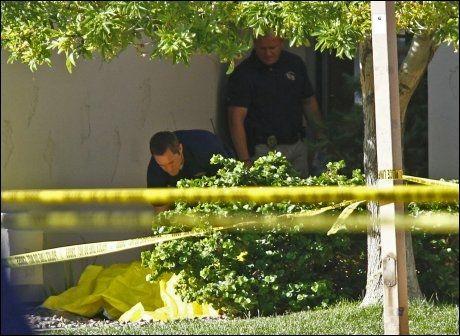 I HAGEN: Politiet undersøkte de tildekkede liket av en av de drepte i hagen utenfor boligen i forstadsområdet Gilbert utenfor Phoenix. Foto: Joshua Lott, Reuters, NTB Scanpix