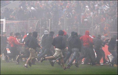 STYGGE SCENER: Rasende Köln-fans stormet banen etter at nedrykket var klart. Foto: AP
