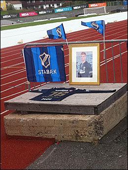 MINNES PÅ NADDERUD: Disse flaggene, dette bildet og denne drakten ble lagt ut på Nadderud til minne om Tor Marius Gromstad i formiddag. Foto: Wegard Bakkehaug