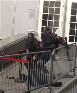 SLUKKER: To polititjenestemenn jobber må slukke den flammene på mannen. Foto: VGTV