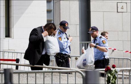 BESLAG: Politi og sikkerhetsvakter undersøker gjenstander på stedet, etter at mannen som satte fyr på seg selv var fraktet bort. Foto: Berit Roald / NTB Scanpix