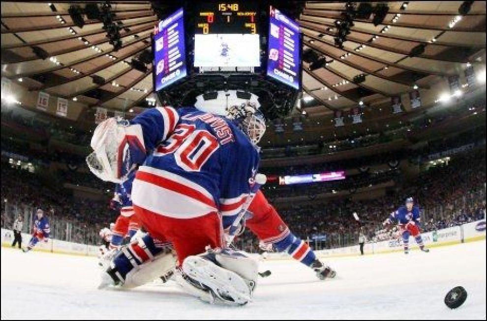 BAKLENGS: New York Rangers svenske målvakt, Henrik Lundquist, må erkjenner at han ikke klarer å stoppe skuddet fra New Jersey Devils Patrik Elias i nattens kamp i Madison Square Garden. Foto: AFP