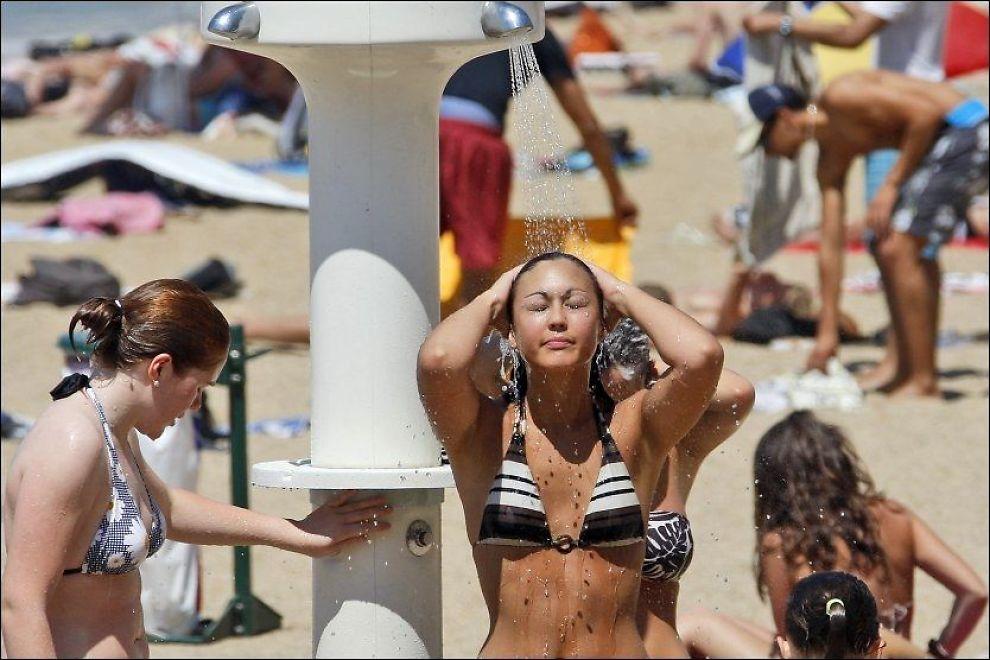 26 GRADER: Turisten Christelle Lavarda frisket opp med en dusj på stranda i Biarritz sørvest i Frankrike da gradestokken viste 26 grader i juni 2009. Langs Middelhavet blir temperaturene gjerne langt høyere enn det. Foto: AP