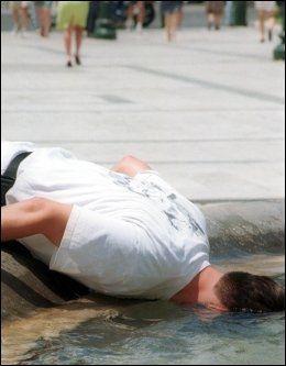 FONTENE-REDNING: Denne mannen i Athen dyppet hodet i en fontene for å avkjøle seg da temperaturen nådde 45 grader i Hellas i juli 2000. Foto: AP