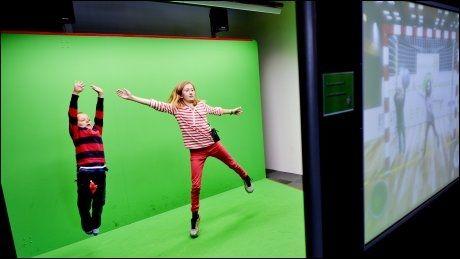 KEEPERTRENING: Stine Axelsen (12) og Stian Bjordal (7 og et halvt) prøver å redde imaginære håndballskudd, som de får mot seg via dataanimasjon. På skjermen til høyre kan tilskuerne se om de klarer å redde skuddene. Foto: Gøran Bohlin