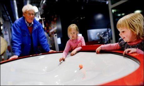 KOSER SEG: - Vi kommer hit så ofte vi bare kan, sier Helge Dyrnes. Sammen med barnebarna Oda og Eira triller de små baller på et «humpete» brett, der de skal prøve å holde ballene i bevegelse lengst mulig. Foto: Gøran Bohlin