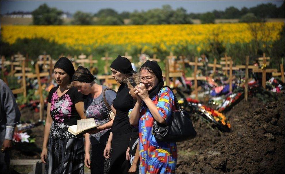 SØRGER: Venner og familie av Petre Ostapenko (35) som døde i flommen, sørger ved graven hans i Krymsk, sør i Russland. Mandag ble det erklært landesorg i landet. Foto: Evard Kornijenko / Reuters / NTB scanpix
