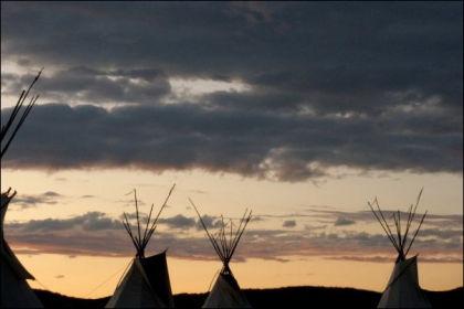 SOLNEDGANG: Solen går ned over tipiteltene i Pine Ridge-reservatet i South-Dakota. Foto: Privat