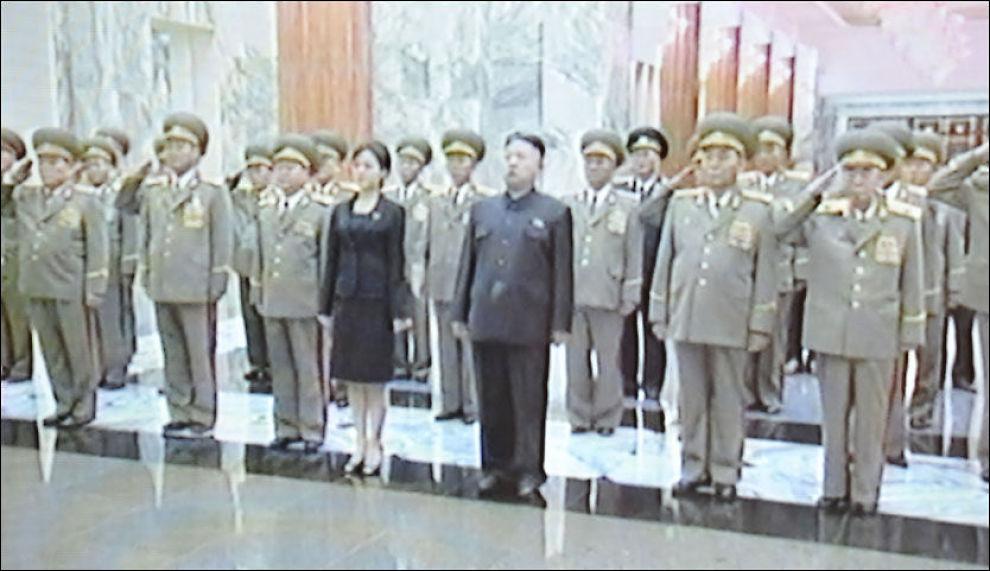 VEKKER OPPSIKT: Internasjonale medier har kastet seg rundt for å finne ut hvem denne kvinnen er. Men foreløpig er Kim Jong-uns kvinnelige ledsager en godt bevart hemmelighet. Foto: NORTH KOREAN TV / AFP