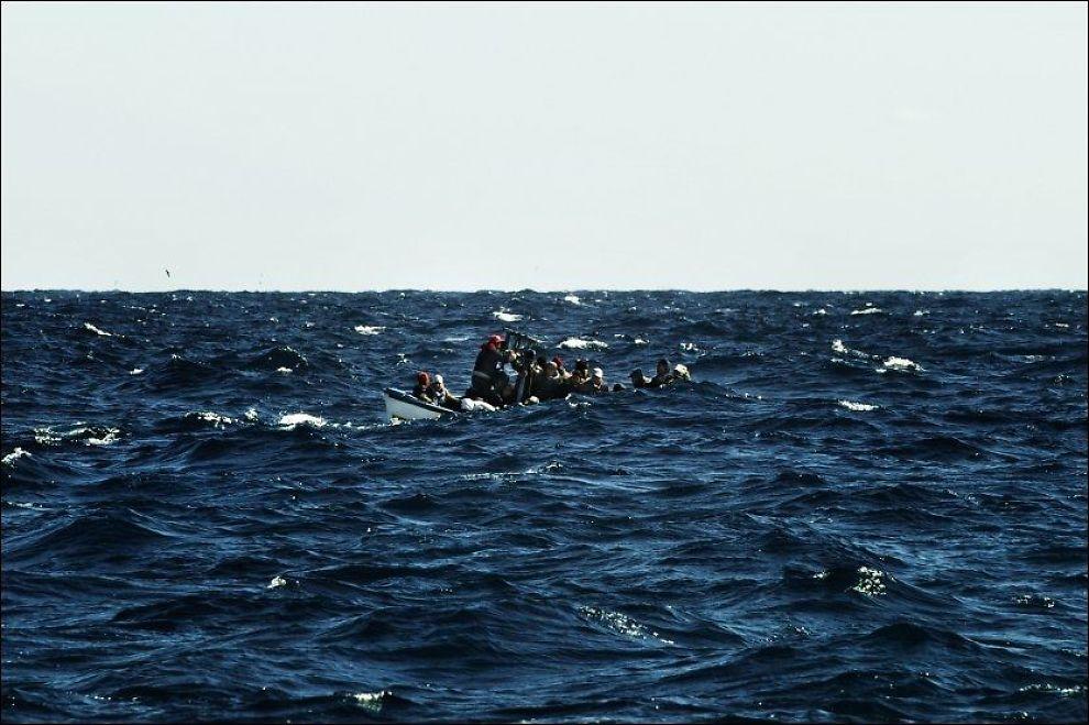 SMUGLES INN: Mange asylsøkere betaler store smmer for en farefull ferd til Europa. Her kommmer flyktninger i båt til Lampedusa, en øy sør i Italia. Foto: AFP