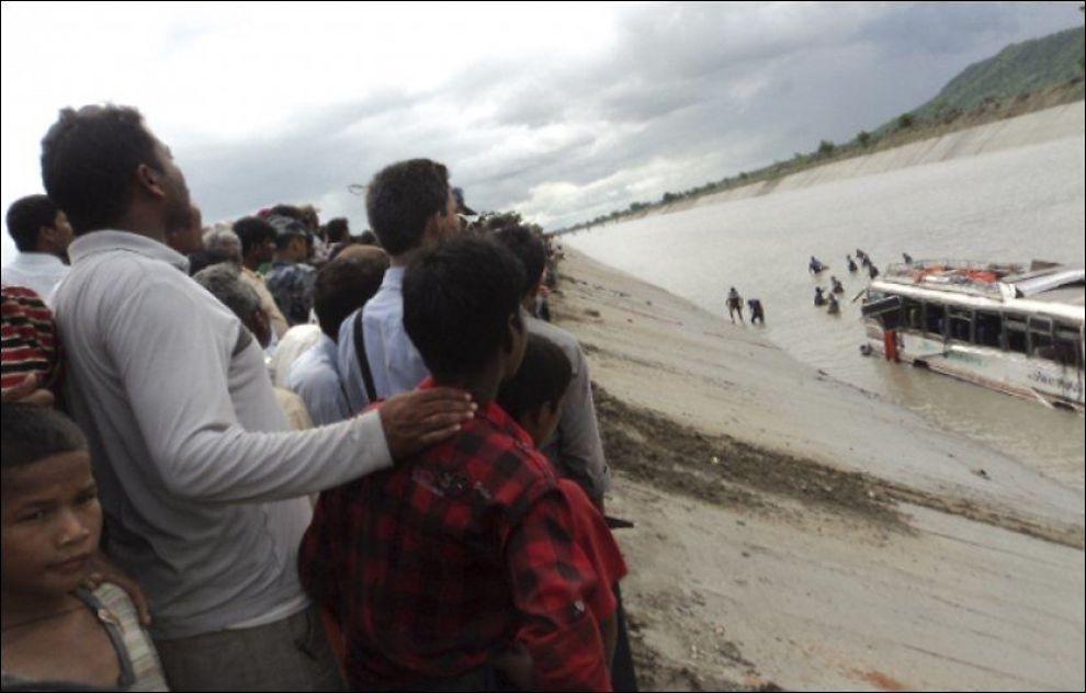 MANGE DØDE: Flere tilskuere ser på at redningsarbeidere leter etter overlevende ved ulykkesbussen. Foto: Stringer, Reuters, NTB Scanpix