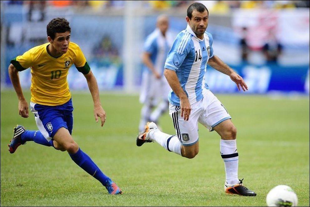 TIL ENGLAND: Oscar (20), her i duell med Javier Mascherano, skal være nær en overgag til Chelsea. Torsdag ankommer han London sammen med Brasils OL-tropp. Foto: Afp