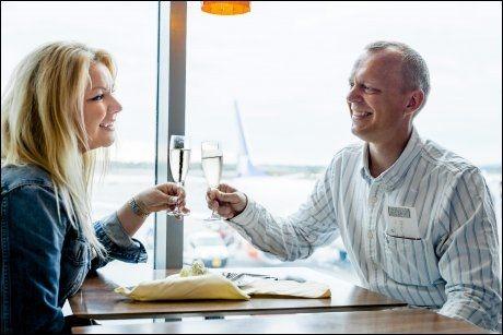 CHAMPAGNEFROKOST: Gaute og June Kjærstad (44) fra Lillestrøm feirer feriestarten med champagnefrokost på Seafood Bar på Gardemoen før klokken har fylt 07.00. Foto: Krister Sørbø