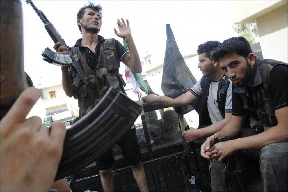 KLARE: Syriske opprørere sitter på lasteplanet til en bil i Aleppo lørdag og gjør seg klare for kamp. Foto: AP