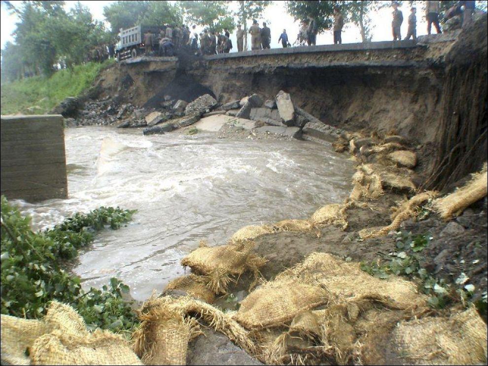 RAMMET AV FLOM: Nordkoreanere jobber med å reparere en bro som ble av flommen 20. juli. Foto: REUTERS