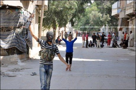 I OPPRØR: Syriske opprørsstyrker vifter med våpen i Salhin-distriktet i byen Aleppo i Syria. Foto: Afp