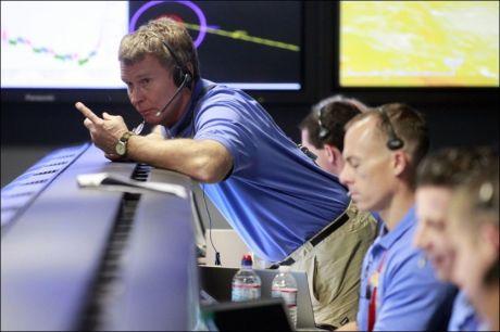 NERVEPIRRENDE: Mandag morgen norsk tid så alt ut til å gå etter planen. Ingeniør Peter Ilott (stående) er en av de som fulgte landingen nøye fra NASAs lokaler i Pasadena. Foto: Reuters