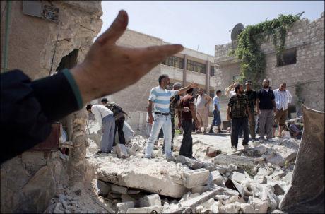 I RUINER: Syriske menn samles utenfor en bombet bygning i Aleppo. Bygningen skal ha blitt truffet da de syriske militærstyrkene forsøkte å treffe de syriske opprørernes hovedkvarter. Foto: Achilleas Zavallis/Afp
