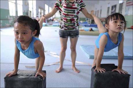 TØYER: To kinesiske jenter får hjelp av en trener på en sportsskole i Nanjing. Foto: AP