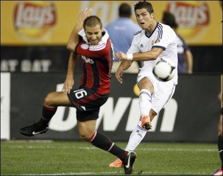 SKUDDVILLIG: Cristiano Ronaldo skyter forbi Milans Mathieu Flamini, som vender rumpa til. Foto: Adam Hunger, Reuters