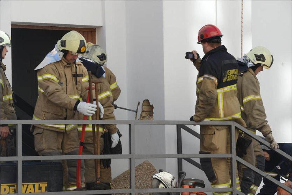 MEISLES UT: Innbrudstyven måtte hakkes ut av skorsteinen han satt i. Utbyttet av innbruddet han planla ble ikke like fruktbart som han håpet på, da brannvesen, politi, skuelystne og presse ventet i hopetall utenfor Danske Bank-bygningen på Fredriksborg. Foto: Kenneth Meyer
