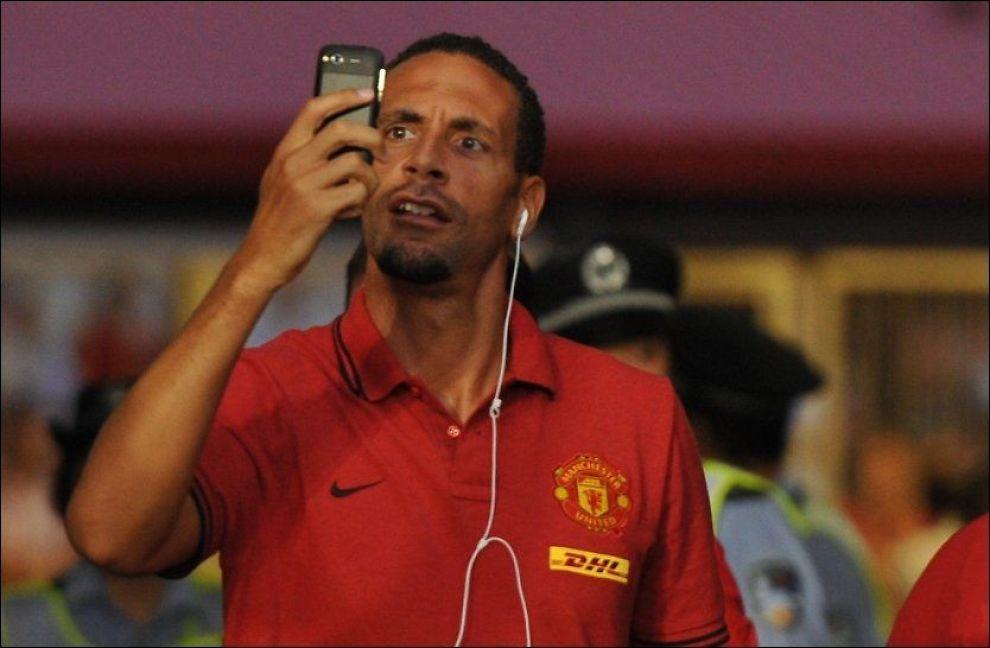 MÅ BETALE: Rio Ferdinand ser på mobilen sin i Shanghai i Kina 24. juli i år. Foto: Peter Parks, AFP